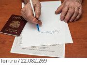 Купить «Пожилой мужчина пишет заявление на листке бумаги на фоне свидетельства о праве на наследство», эксклюзивное фото № 22082269, снято 3 марта 2016 г. (c) Игорь Низов / Фотобанк Лори