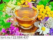 Tea from flowers in glass cup on dark board. Стоковое фото, фотограф Zoonar/kostrez / easy Fotostock / Фотобанк Лори