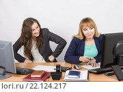 Офисная работница с наигранным возмущением смотрит на коллегу, сидящую рядом за компьютером с невинным видом. Стоковое фото, фотограф Иванов Алексей / Фотобанк Лори
