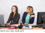 Купить «Офисная работница с возмущением смотрит на довольную коллегу, сидящую рядом за компьютером», фото № 22124221, снято 30 января 2016 г. (c) Иванов Алексей / Фотобанк Лори