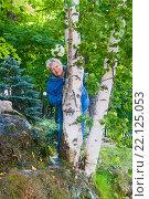 Купить «Улыбающаяся пожилая женщина выглядывает  из-за ствола березы», фото № 22125053, снято 20 августа 2015 г. (c) Наталья Федорова / Фотобанк Лори