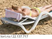 Купить «Молодая загорелая девушка на пляже лежит на шезлонге на животе», фото № 22137717, снято 20 сентября 2015 г. (c) Иванов Алексей / Фотобанк Лори