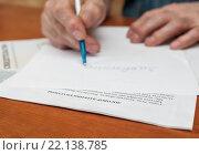 Купить «Взрослый мужчина пишет заявление на листке бумаги лежащее на договоре дарения квартиры», эксклюзивное фото № 22138785, снято 3 марта 2016 г. (c) Игорь Низов / Фотобанк Лори