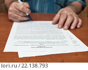 Купить «Немолодой мужчина ставит подпись под договором купли-продажи квартиры», эксклюзивное фото № 22138793, снято 3 марта 2016 г. (c) Игорь Низов / Фотобанк Лори