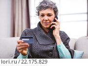 Купить «Mature woman holding credit card while talking on mobile phone», фото № 22175829, снято 20 ноября 2015 г. (c) Wavebreak Media / Фотобанк Лори