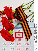 Купить «Георгиевская ленточка и красные гвоздики на календаре с датой 9 мая - День Победы», фото № 22199677, снято 13 марта 2016 г. (c) Зезелина Марина / Фотобанк Лори