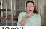 Купить «Молодая женщина сидит на лестнице дома и чихает, прикрывая рот руками», видеоролик № 22200461, снято 15 марта 2016 г. (c) Кекяляйнен Андрей / Фотобанк Лори