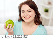 Купить «happy plus size woman eating green apple at home», фото № 22225521, снято 21 февраля 2016 г. (c) Syda Productions / Фотобанк Лори