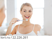 Купить «woman with toothbrush cleaning teeth at bathroom», фото № 22226261, снято 13 февраля 2016 г. (c) Syda Productions / Фотобанк Лори
