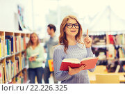 happy student girl or woman with book in library. Стоковое фото, фотограф Syda Productions / Фотобанк Лори