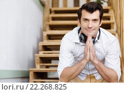 Купить «Portrait of young man sitting at the stairs in office», фото № 22268825, снято 14 апреля 2015 г. (c) Sergey Nivens / Фотобанк Лори