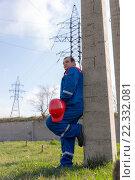 Мужчина электрик в спецодежде с каской в руке стоит у бетонного столба. Стоковое фото, фотограф Станислав Илюк / Фотобанк Лори