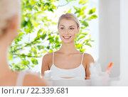 happy young woman looking to mirror at bathroom. Стоковое фото, фотограф Syda Productions / Фотобанк Лори