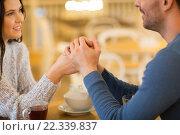 Купить «happy couple with tea holding hands at restaurant», фото № 22339837, снято 23 января 2016 г. (c) Syda Productions / Фотобанк Лори