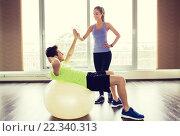 Купить «smiling man and woman with exercise ball in gym», фото № 22340313, снято 5 апреля 2015 г. (c) Syda Productions / Фотобанк Лори