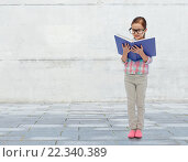 Купить «happy little girl in eyeglasses reading book», фото № 22340389, снято 31 января 2016 г. (c) Syda Productions / Фотобанк Лори