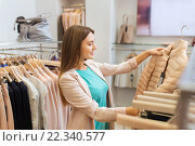 Купить «happy young woman choosing clothes in mall», фото № 22340577, снято 19 февраля 2016 г. (c) Syda Productions / Фотобанк Лори