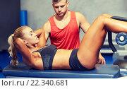 Купить «woman with personal trainer doing sit ups in gym», фото № 22340681, снято 19 апреля 2015 г. (c) Syda Productions / Фотобанк Лори