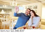 Купить «couple taking smartphone selfie at cafe restaurant», фото № 22340837, снято 23 января 2016 г. (c) Syda Productions / Фотобанк Лори