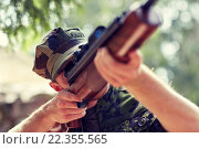 Купить «soldier or hunter shooting with gun in forest», фото № 22355565, снято 14 августа 2014 г. (c) Syda Productions / Фотобанк Лори