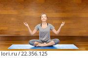 woman making yoga meditation in lotus pose on mat. Стоковое фото, фотограф Syda Productions / Фотобанк Лори