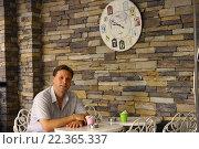 Человек ждет завтрак за столиком кафе. Стоковое фото, фотограф Наталья Данченко / Фотобанк Лори