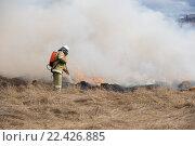 Купить «Пожарный тушит горящую сухую траву из ранцевого лесного огнетушителя на фоне дыма и домов», фото № 22426885, снято 1 апреля 2016 г. (c) Игорь Малеев / Фотобанк Лори