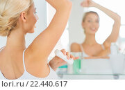 Купить «woman with antiperspirant deodorant at bathroom», фото № 22440617, снято 13 февраля 2016 г. (c) Syda Productions / Фотобанк Лори