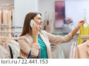 Купить «woman calling on smartphone at clothing store», фото № 22441153, снято 19 февраля 2016 г. (c) Syda Productions / Фотобанк Лори