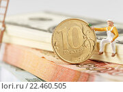 Купить «Человечек сидит на пачке долларов и касается рукой 10-рублевой монеты», эксклюзивное фото № 22460505, снято 1 апреля 2016 г. (c) Юрий Шурчков / Фотобанк Лори