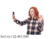 Купить «Радостная рыжеволосая девушка фотографирует себя на мобильный телефон», фото № 22461049, снято 30 мая 2020 г. (c) Максим Бейков / Фотобанк Лори