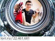 Купить «Парень загружает одежду в стиральную машину», фото № 22461681, снято 5 июня 2020 г. (c) Кузнецов Дмитрий / Фотобанк Лори
