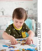 Купить «Маленький мальчик, 2,5 года, собирает пазл сидя за столом», фото № 22515897, снято 20 марта 2016 г. (c) Юлия Бабкина / Фотобанк Лори
