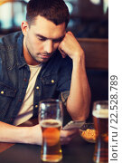 man with smartphone drinking beer at bar, фото № 22528789, снято 22 апреля 2015 г. (c) Syda Productions / Фотобанк Лори