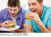 Купить «close up of friends eating hamburgers at home», фото № 22529169, снято 22 марта 2014 г. (c) Syda Productions / Фотобанк Лори