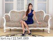 Девушка в синем платье сидит на диване. Стоковое фото, фотограф Литвяк Игорь / Фотобанк Лори