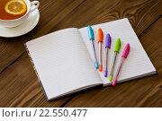 Открытый ежедневник с разноцветными ручками и чашка чая с лимоном на деревянном столе. Стоковое фото, фотограф Елена Фомичева / Фотобанк Лори
