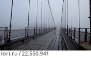 Купить «Man walking on hinged bridge through the Katun river near the village of Multa», видеоролик № 22550941, снято 11 апреля 2016 г. (c) Serg Zastavkin / Фотобанк Лори