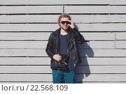 Модный фотограф с фотоаппаратом в кожаной куртке (2016 год). Редакционное фото, фотограф Юрий Коваль / Фотобанк Лори