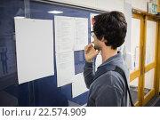 Купить «Student reading notice board», фото № 22574909, снято 30 июля 2015 г. (c) Wavebreak Media / Фотобанк Лори