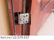 Купить «Рваный метал на петлях дешевой двери», фото № 22579537, снято 18 марта 2016 г. (c) Иванов Алексей / Фотобанк Лори