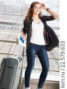Девушка стоит с чемоданом, паспортом и билетом. Стоковое фото, фотограф Riasna Yuliia / Фотобанк Лори