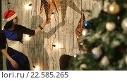 Купить «Девушка украшает комнату на Рождество», видеоролик № 22585265, снято 26 ноября 2015 г. (c) Виктор Аллин / Фотобанк Лори