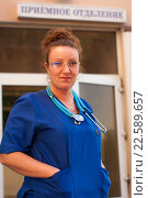 Портрет улыбающейся женщины врача со стетоскопом на фоне приемного отделения, фото № 22589657, снято 20 сентября 2014 г. (c) Эдуард Паравян / Фотобанк Лори