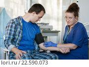 Женщина врач измеряет давление у мужчины пациента и смотрит в камеру, фото № 22590073, снято 20 сентября 2014 г. (c) Эдуард Паравян / Фотобанк Лори