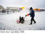 Мужчина убирает снег во дворе снегоуборочной машиной (2016 год). Редакционное фото, фотограф Алексей Маринченко / Фотобанк Лори