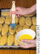 Смазывание сырых пирожков яйцом. Стоковое фото, фотограф Михаил Степанов / Фотобанк Лори
