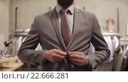 Купить «young man trying suit jacket at clothing store», видеоролик № 22666281, снято 8 апреля 2016 г. (c) Syda Productions / Фотобанк Лори