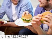 Купить «close up of friends eating hamburgers at home», фото № 22670237, снято 22 марта 2014 г. (c) Syda Productions / Фотобанк Лори