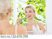 Купить «woman with toothbrush cleaning teeth at bathroom», фото № 22670705, снято 13 февраля 2016 г. (c) Syda Productions / Фотобанк Лори